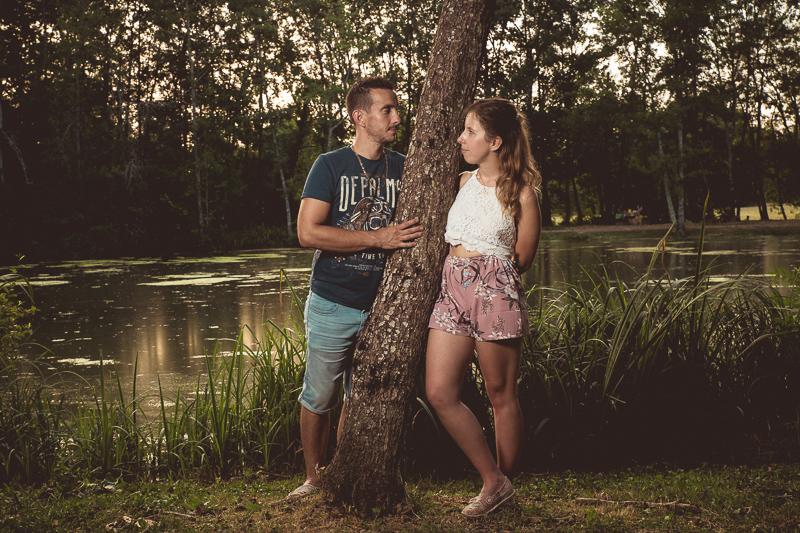 Jeune couple se regardant dans les yeux devant une étendue d'eau