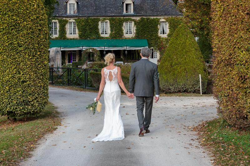 couple de mariés de dos à l'entrée du Manoir