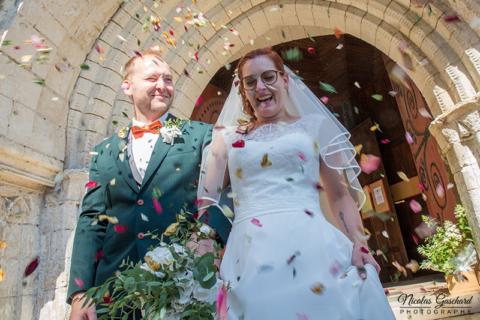 Couple de jeunes mariés à la sortie de l'Abbaye de Brantôme sous le jet de pétales de fleurs