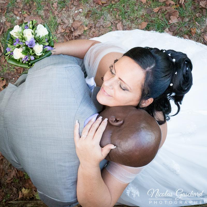 couple de jeunes mariés enlacé avec bouquet de fleurs