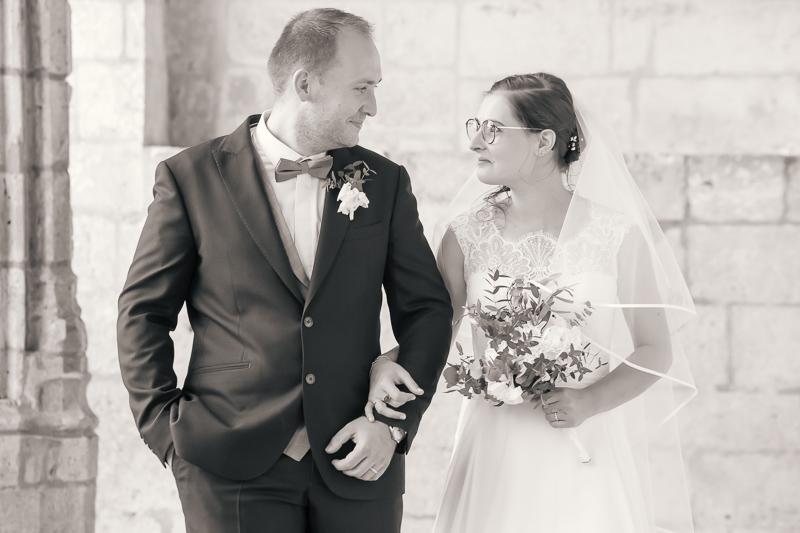 couple de jeunes mariés marchant bras dessus bras dessous abbaye de Brantôme